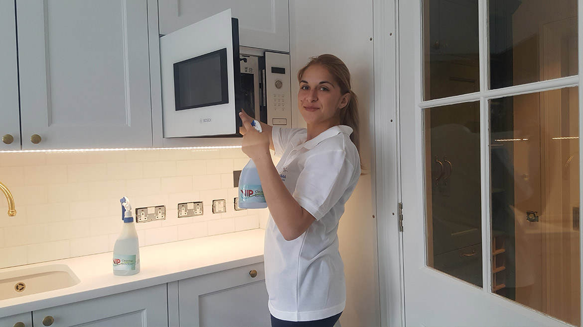 Our girl cleaner in kitchen cleaning the microwave